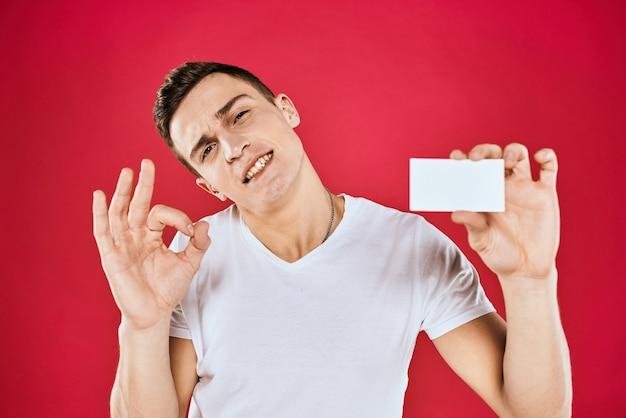 Un hombre con una camiseta blanca con una tarjeta de presentación en sus manos emociones pared roja.
