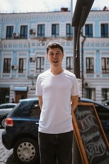 Hombre en camiseta gris y jeans sobre fondo de calle de la ciudad
