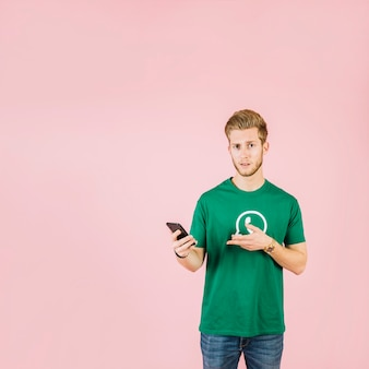 Hombre con camiseta de icono de whatsapp gesticulando mientras sostiene el teléfono móvil