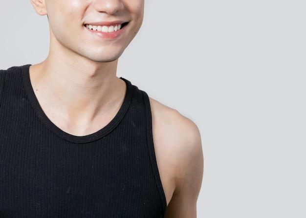 Hombre en camiseta sin mangas sonriendo y posando