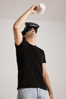 Un hombre con camiseta negra en blanco y casco de realidad virtual está mirando hacia una taza blanca vacía que sostiene sobre su cabeza, aislado en blanco