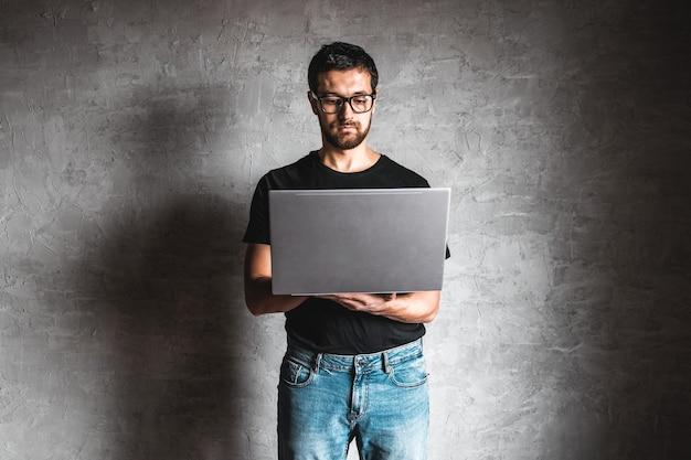 Hombre con una camiseta negra con un portátil sobre un fondo gris. educación, éxito, conocimiento