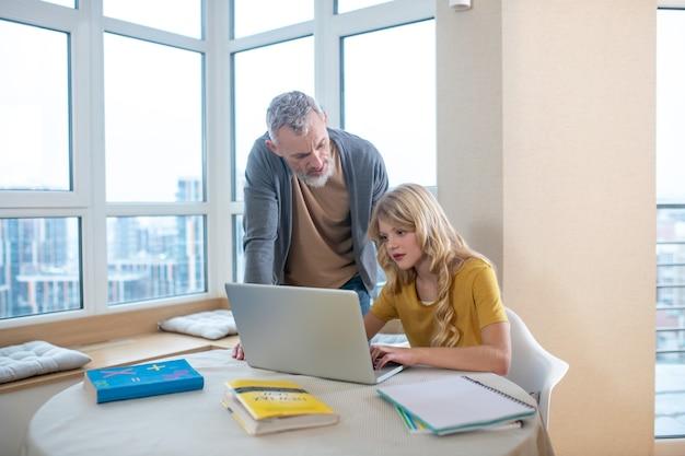 Un hombre canoso de pie junto a su hija mientras ella trabaja en la computadora portátil