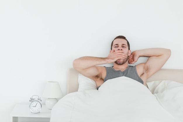 Hombre cansado bostezando mientras se despierta