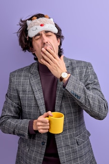 Hombre cansado bostezando sosteniendo una taza amarilla, con antifaz para dormir.