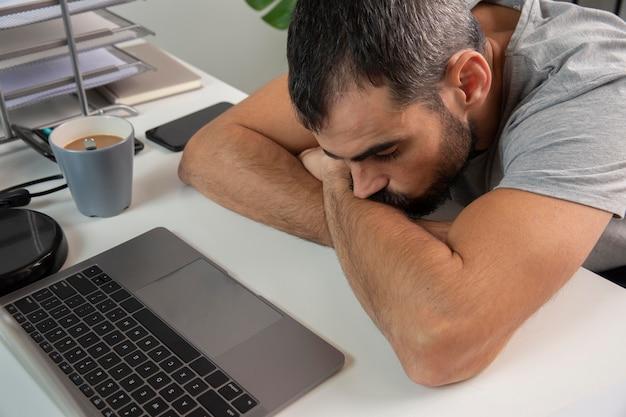 Hombre cansado con la cabeza apoyada en el escritorio en casa