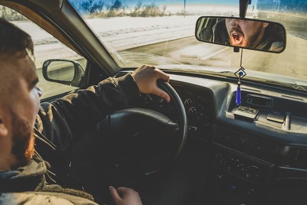 Hombre cansado de ir y bosteza en el auto