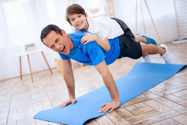 Hombre cansado con el niño en la espalda wrung fuera del piso.