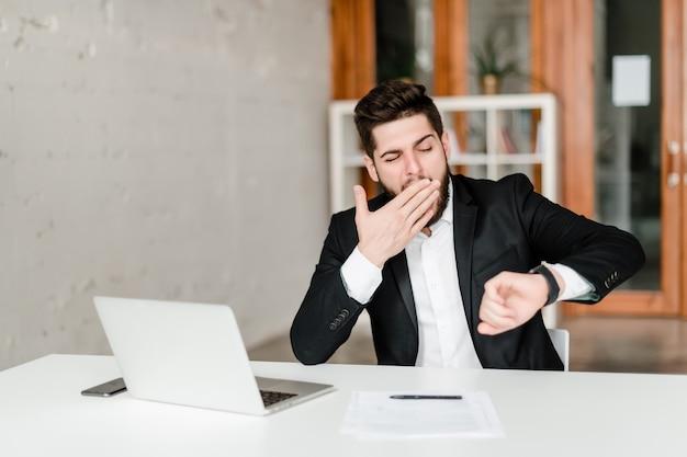 Hombre cansado en la oficina bosteza y controla el tiempo en su reloj