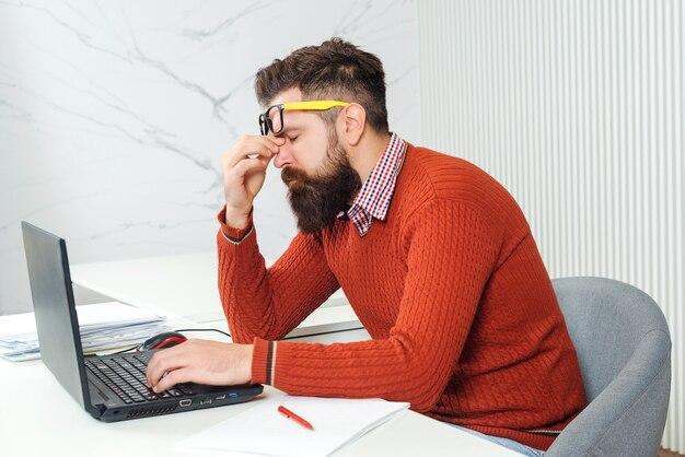Hombre cansado con ordenador portátil en el lugar de trabajo. hombre barbudo con exceso de trabajo en la oficina. destacó el apuesto hombre de negocios. sentirse cansado. hombre joven que tiene tiempo estresante trabajando en la computadora portátil