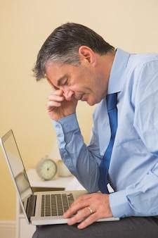 Hombre cansado que usa una computadora portátil que se sienta en una cama