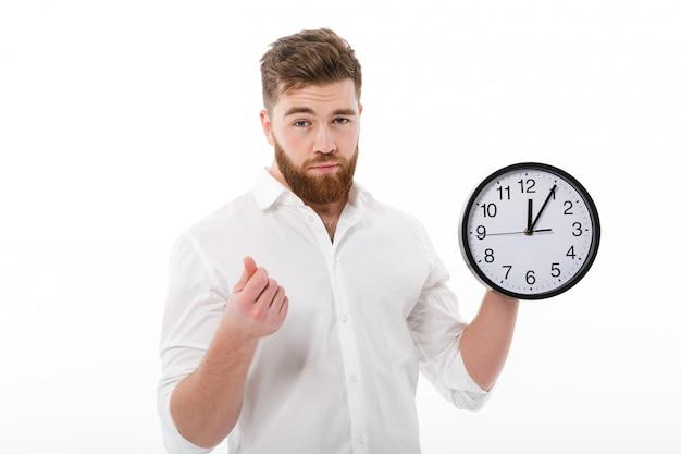 Hombre cansado en ropa de negocios que muestra el tiempo es gesto de dinero
