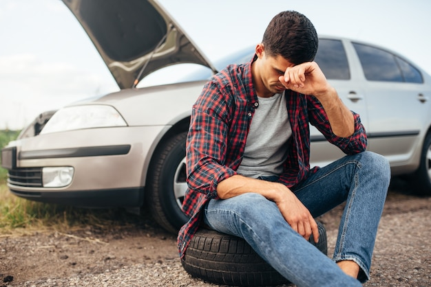 Hombre cansado sentado en el neumático, coche roto con capó abierto
