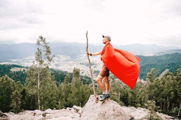 Hombre en capa roja de pie en la cima de la montaña con paisaje natural