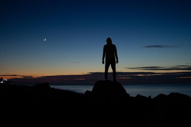 Hombre en el capó de pie sobre las rocas en el fondo del mar en el tiempo de la tarde
