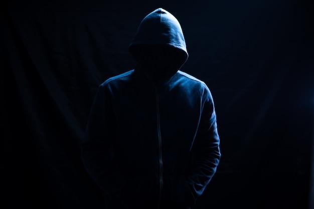 Un hombre con capucha está parado en negro.