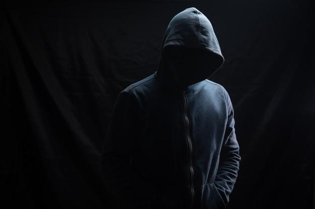 Un hombre con capucha está parado sobre un fondo negro