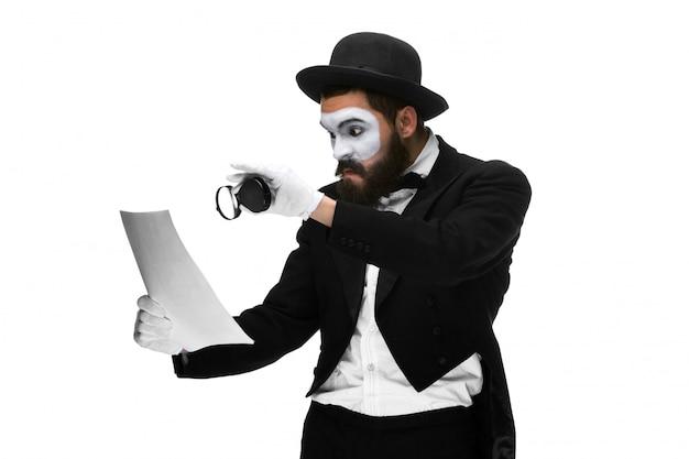 Hombre con una cara mimo leyendo con lupa