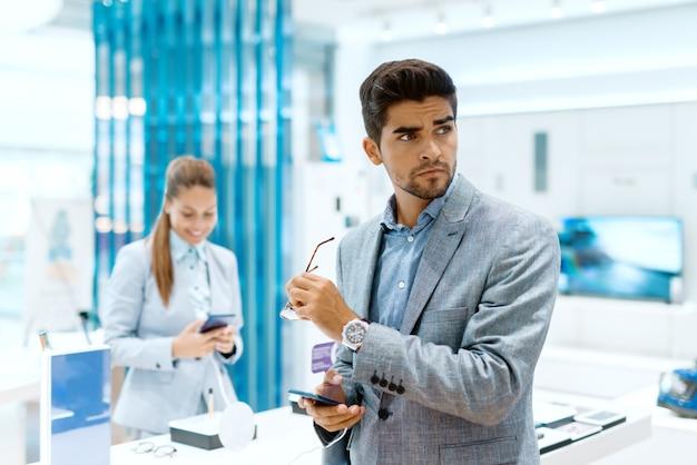 Hombre con cara seria mirando a otro lado mientras sostiene el teléfono inteligente en una mano y anteojos en otra
