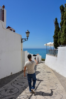 Hombre con cardán para smartphone caminando por las calles de una ciudad mediterránea