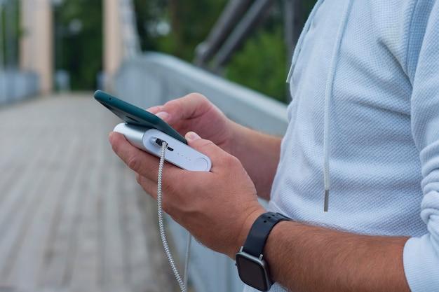 El hombre carga un teléfono inteligente con un banco de energía en la mano. cargador portátil para cargar dispositivos.