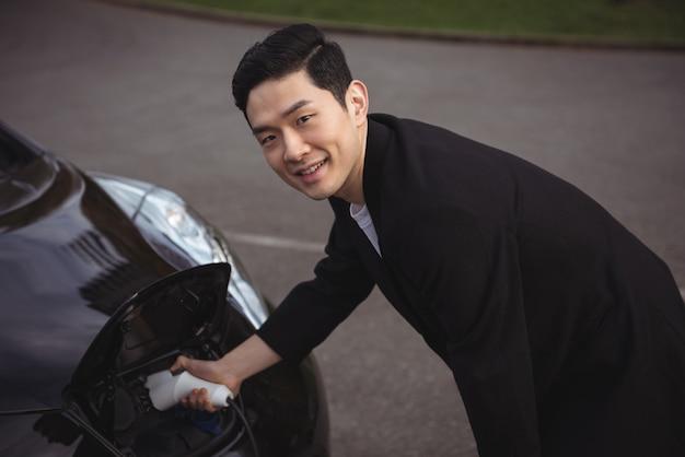 Hombre cargando el coche en la estación de carga de vehículos eléctricos