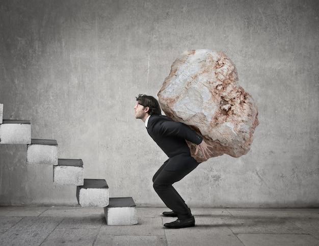 Hombre cargando una piedra grande