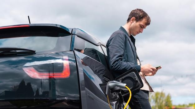 Hombre cargando su coche eléctrico en la estación de carga y usando smartphone