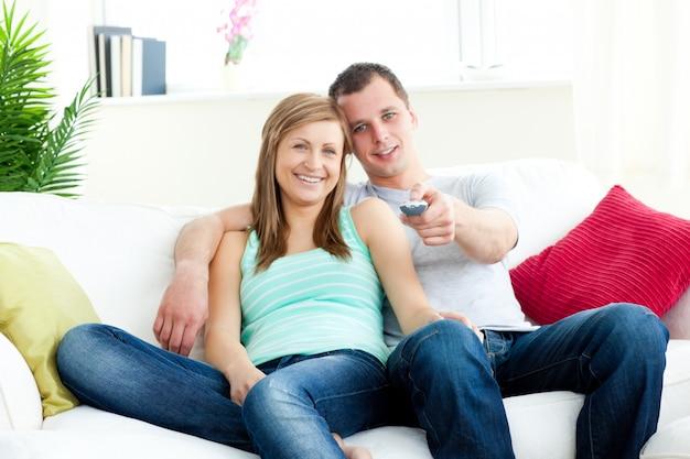 Hombre cariñoso abrazando a su novia mientras ve la televisión