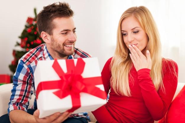 Hombre cariñoso dando a su novia regalo de navidad