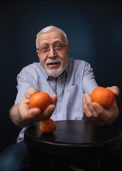 Hombre carismático en edad y con gafas, extiende sus manos en el marco con mandarinas naranjas,