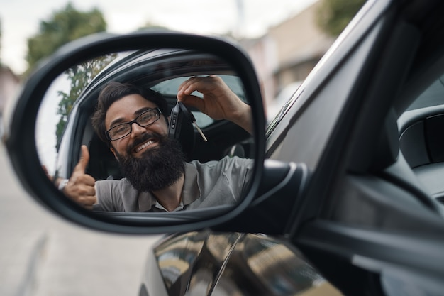 Hombre carismático que sostiene las llaves del auto