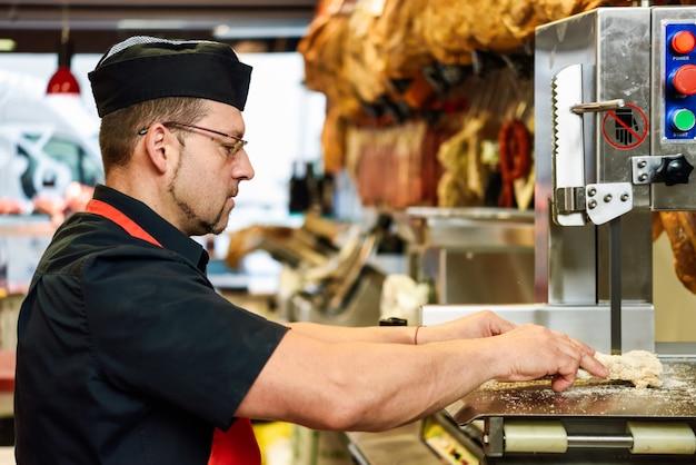 Hombre carnicero cortando huesos de jamón en una máquina cortadora