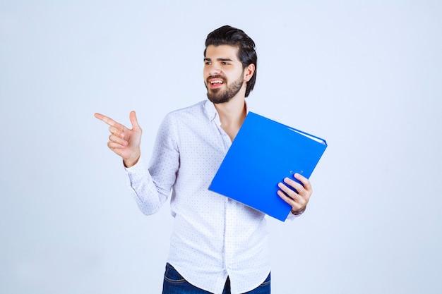 Hombre con una carpeta azul presentando a su colega de la izquierda