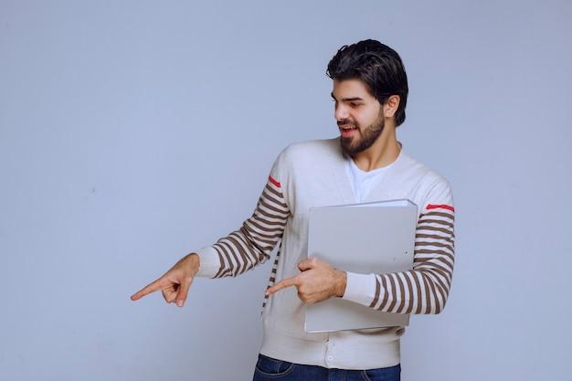 Hombre con una carpeta de informes y señalando a alguien de la izquierda.