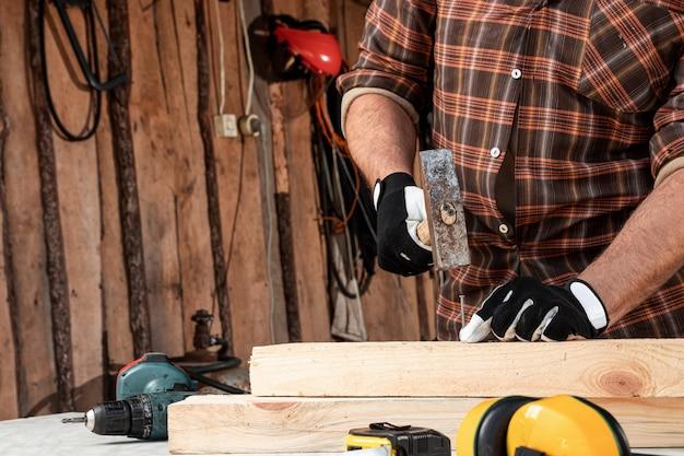 Un hombre carpintero clava un clavo en un árbol, manos masculinas con un martillo de cerca. carpintería