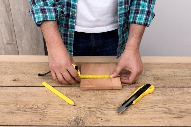 Hombre carpintero con regla y cortador