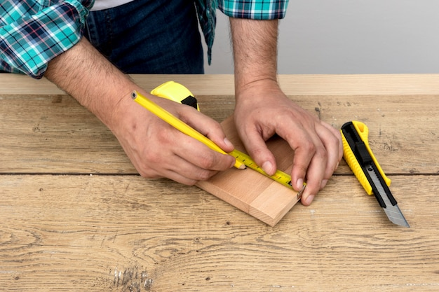 Hombre carpintero con regla y lápiz