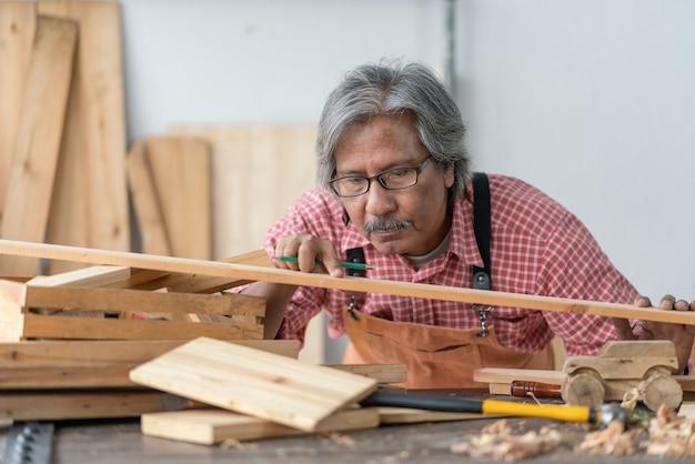 Hombre carpintero senior asiático mirando tablón de madera en el taller de carpintero