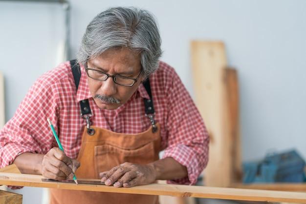 Hombre carpintero senior asiático con regla medir a escala en la plancha de madera en el taller