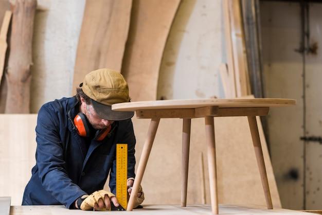 Hombre carpintero tomando medidas de mesa de madera con regla