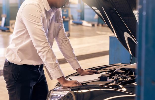 Este hombre de carrera saleman inspección de negocios escribiendo una nota en el bloc de notas o libro, papel con fondo borroso coche