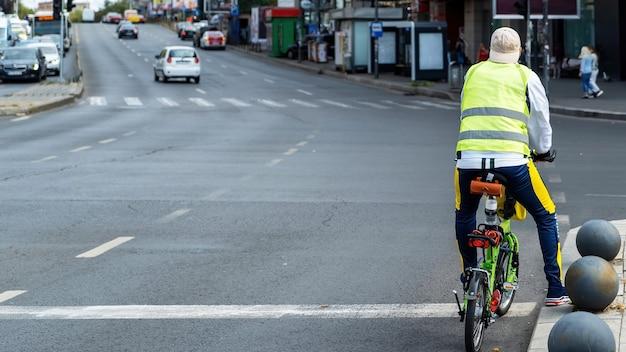 Hombre en la carretera en una pequeña bicicleta verde, calle con coches y personas