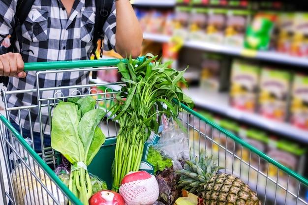 Hombre con carrito de compras comprando alimentos en un supermercado. detalle del primer del carro de compras.