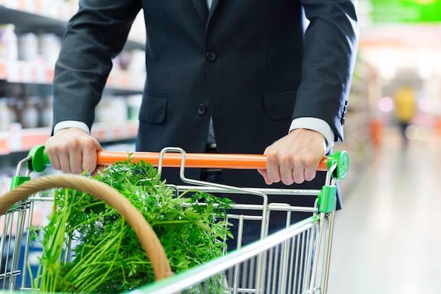Hombre con carrito de compras en supermercado