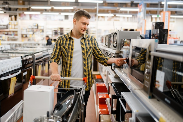 Hombre con carro eligiendo microondas en tienda de electrónica. persona de sexo masculino comprando electrodomésticos en el mercado