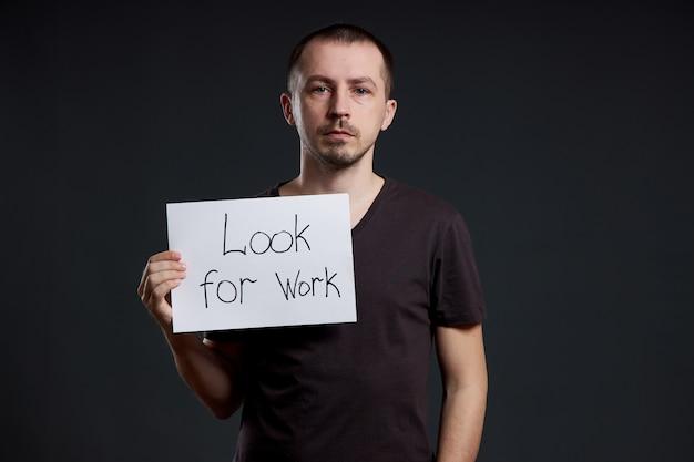 Hombre con un cartel con las palabras buscar trabajo