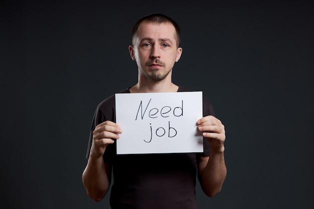 Hombre con un cartel con las palabras necesita trabajo