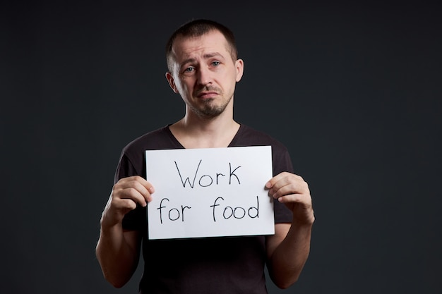 Hombre con un cartel con las palabras trabajar por comida