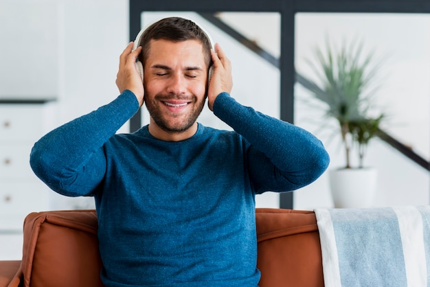 Hombre en casa en el sofá escuchando música